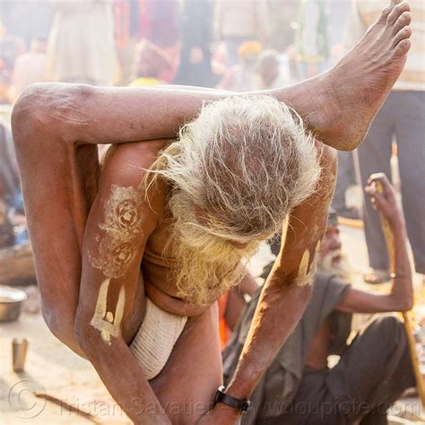 yogi sadhu in yoga position standing with leg behind the